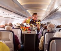 EP0ET1 A flight attendant member of the cabin crew serving food on a Monarch Airlines airplane from Madeira to Gatwick airport, UK