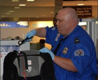 TSA officer checking a carry-on bag for a firearm